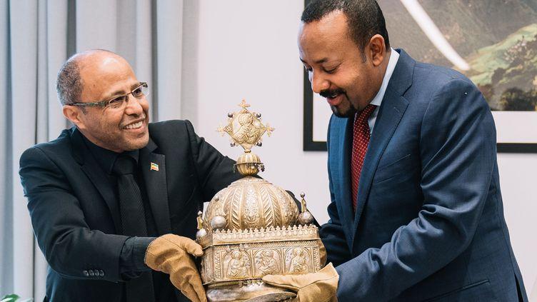 Sirak Asfaw (G) remet au Premier ministre éthiopien Abiy Ahmed la couronne du 18e siècle qu'il a conservée 21 ans aux Pays-Bas (- / ETHIOPIA PRIME MINISTER OFFICE)