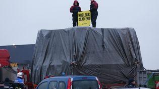 Des militants de l'organisation écologiste Greenpeace qui bloquent le camiontransportant le couvercle de la cuve de l'EPR de Flamanville, le 12 février 2016. (CHARLY TRIBALLEAU / AFP)