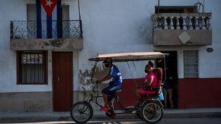 Un taxi transporte une femme à La Havane (Cuba), le 14 juillet 2021. (YAMIL LAGE / AFP)