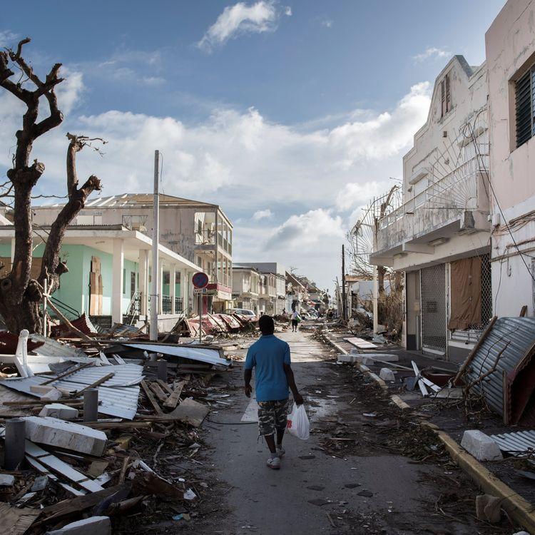 Un homme marche au milieu des dégâts causés par l'ouragan Irma à Marigot (Saint-Martin, France), le 8 septembre 2017. (MARTIN BUREAU / AFP)
