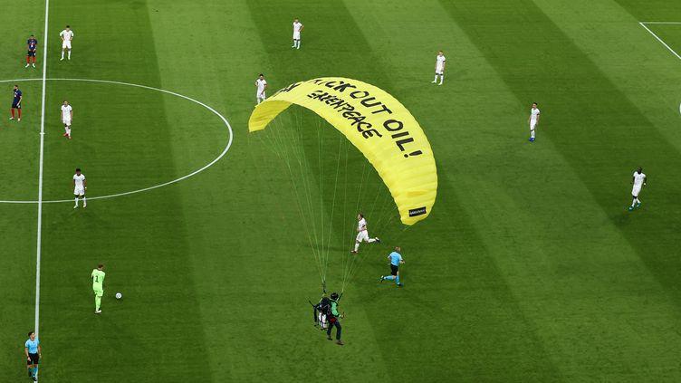 Un militant de Greenpeace se poseavec difficultésur la pelouse de l'Allianz Arena, à Munich, après avoir frôlé une tribune, avant la rencontre entrela France et l'Allemagne,durant l'Euro de football, le 15 juin 2021. (CHRISTIAN CHARISIUS / DPA / AFP)