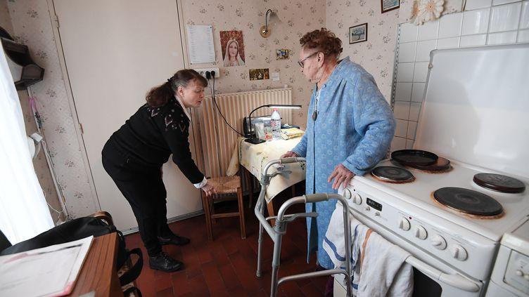 Une aide à domicile auprès d'une personne âgée. (illustration) (FREDERICK FLORIN / AFP)