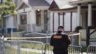 Un policier monte la garde devant la maison dans laquelle ont été découvertes trois jeunes femmes kidnappées dix ans auparavant, à Cleveland (Ohio, Etats-Unis), le 7 mai 2013. (BILL PUGLIANO / GETTY IMAGES NORTH AMERICA / AFP)