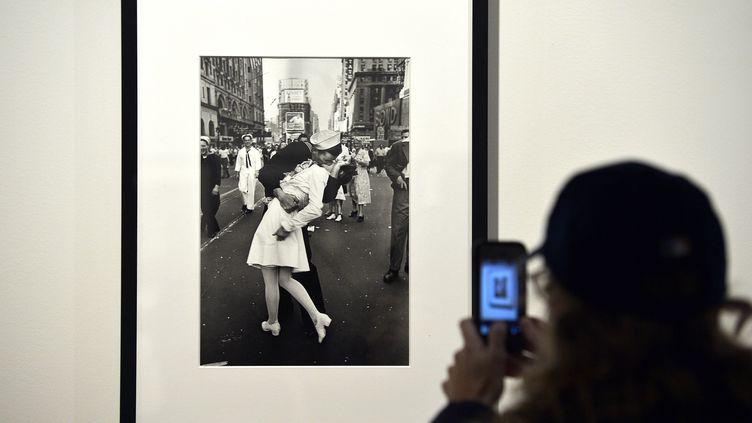 Une personne prend en photo le célèbre cliché du baiser pris par le photographeAlfred Eisenstaedtà Times Square en 1945 après l'annonce de la fin de la Second Guerre mondiale. (GABRIEL BOUYS / AFP)