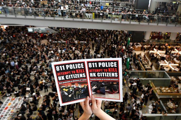 Pour protester contre le projet de loi d'extradition et les violences policières, les manifestants hongkongais envahissent l'aéroport de Hong Kong, le 12 août 2019. (MANAN VATSYAYANA / AFP)