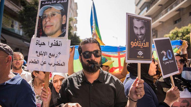 Militants de gauche, syndicalistes et proches des condamnés ont marché pendant deux heures dans le centre de la capitale économique du Maroc sous l'œil des forces de l'ordre qui parlent, elles, de «quelques centaines» de personnes. Brandissant des portraits des meneurs du Hirak, des drapeaux amazigh ou symbolisant le Mouvement du 20 février, ils ont dénoncé un «procès politique» et un «Etat corrompu» et demandé la libération des activistes détenus. De leur côté, les avocats disent craindre pour la santé de Rabie el-Ablak (en casquette sur l'affiche) en grève de la faim depuis 42 jours. (Jalal Morchidi/Agence Anadolu/AFP )