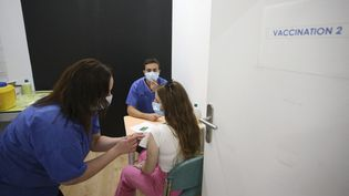 Une jeune femme de 19 ans se fait vacciner contre le Covid-19 à Ajaccio (Corse-du-Sud), le 13 mai 2021. (PASCAL POCHARD-CASABIANCA / AFP)