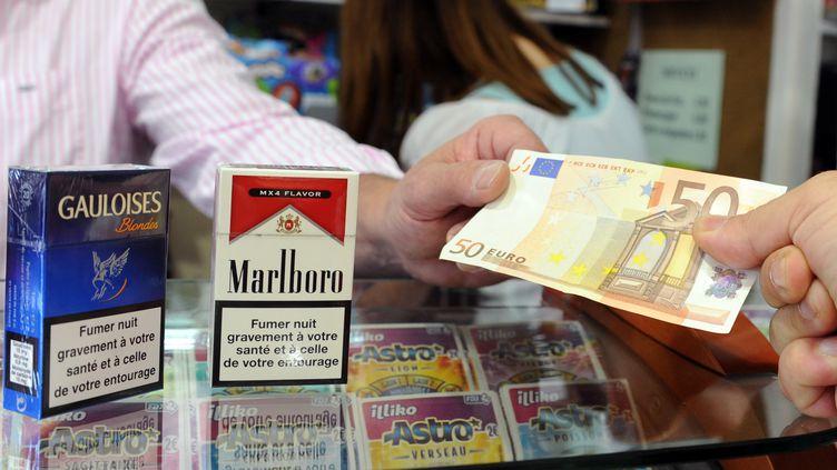 Le 6 septembre 2012, un client règle des paquets de cigarettes dans un bureau de tabac, à Toulouse (Haute-Garonne). (PASCAL PAVANI / AFP)