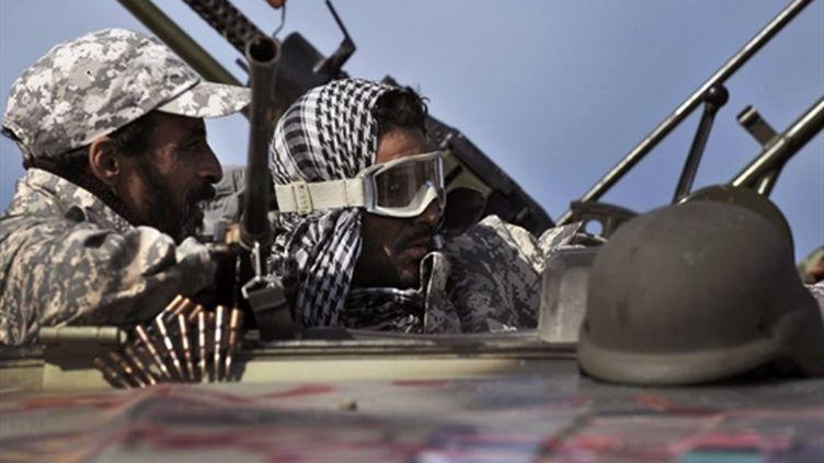 Des insurgés libyens protègent le départ de leurs troupes vers le port pétrolier de Ras Lanouf, le 27 mars 2011 (AFP/ARIS MESSINIS)