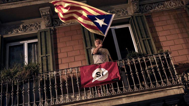 Un homme agite un drapeau catalan en faveur de l'indépendance, le 1er octobre 2017 à Barcelone. (PAU BARRENA / AFP)