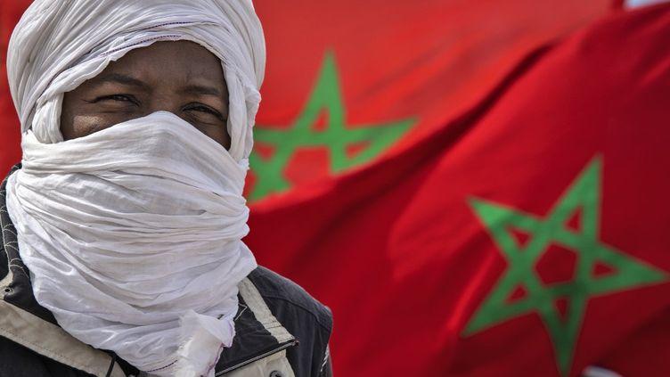 Unhomme avec un drapeau marocain près de la frontière mauritanienne, à Guerguerat, au Sahara occidental, le 26 novembre 2020. (FADEL SENNA / AFP)