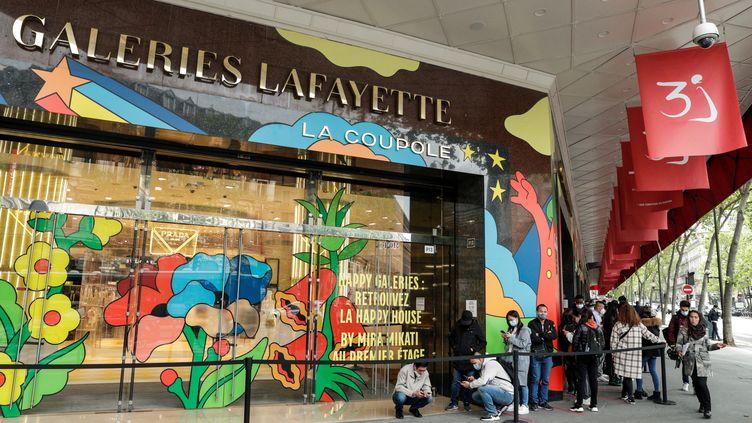 Des personnes font la queue devant les Galeries Lafayette à Paris, le 19 mai 2021. (GEOFFROY VAN DER HASSELT / AFP)