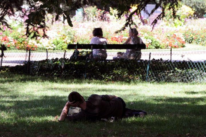 Un homme se repose dans l'herbe d'un parc à Toulouse (Haute-Garonne), le 17 août 2012. (PASCAL PAVANI / AFP)