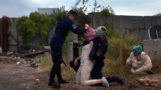Une femme policier à l'uniforme américain, une arrestation musclée, des enfants et des cagoules colorées emblématiques du groupe Pussy Riot, dans le nouveau clip des artistes militantes...  (Capture image YouTube)