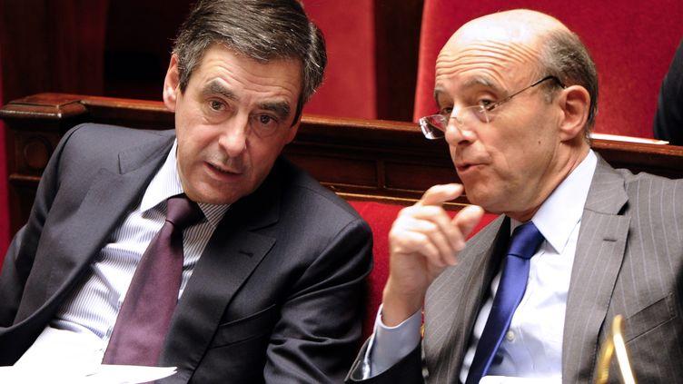 François Fillon, premier ministre, et Alain Juppé, ministre des Affaires étrangères, le 6 décembre 2011, à l'Assemblée nationale, à Paris. (BERTRAND GUAY / AFP)