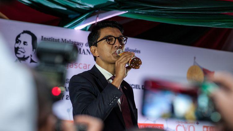 Le président de la République de Madagascar, Andry Rajoelina, prend une gorgée de Covid-Organics, un remède à base de plantes médicinales mis au point par l'Institut malgache de recherches appliquées, devant la presse le 20 avril 2020 à Antananarivo (Madagascar). (HENITSOA RAFALIA / ANADOLU AGENCY)