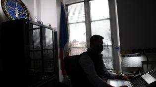 Un gendarme français de l'Office central de lutte contre les crimes contre l'humanité, les génocides et les crimes de guerre (OCLCH), travaille dans son bureau, le 21 janvier 2021 à Paris. (ALAIN JOCARD / AFP)