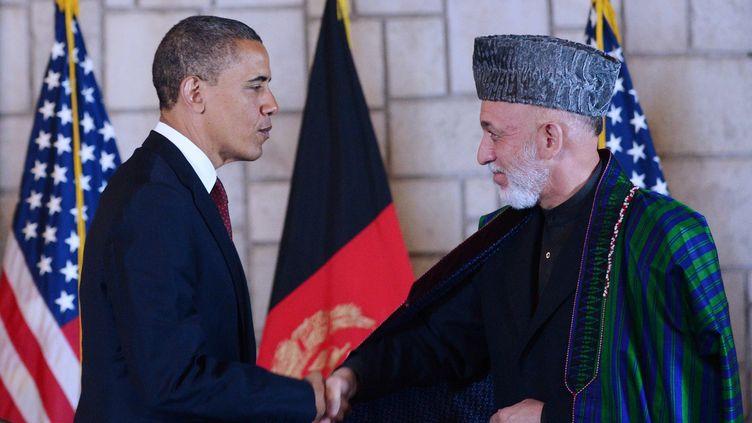 Le président américain, Barack Obama, en visite surprise à Kaboul (Afghanistan), serre la main du président afghan, Hamid Karzaï, le 1er mai 2012. (MANDEL NGAN / AFP)