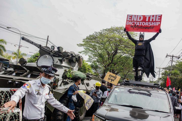 """Un manifestant déguisé en Batman tient une pancarte sur laquelle est écrit """"Mettez fin à la dictature en Birmanie"""", le 15 février 2021 à Rangoun (Birmanie). (SOPA IMAGES / LIGHTROCKET / GETTY IMAGES)"""