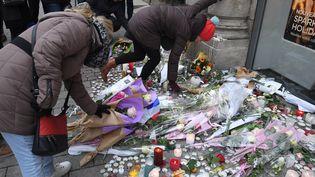 Des passants déposent des fleurs et des bougies en hommage aux victimes de l'attentat de Strasbourg, le 14 décembre 2018. (PATRICK HERTZOG / AFP)
