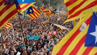Des partisans de l'indépendance de la Catalogne regardent la session du Parlement catalan sur des écrans géants à Barcelone, le 27 octobre 2017. (YVES HERMAN / REUTERS)