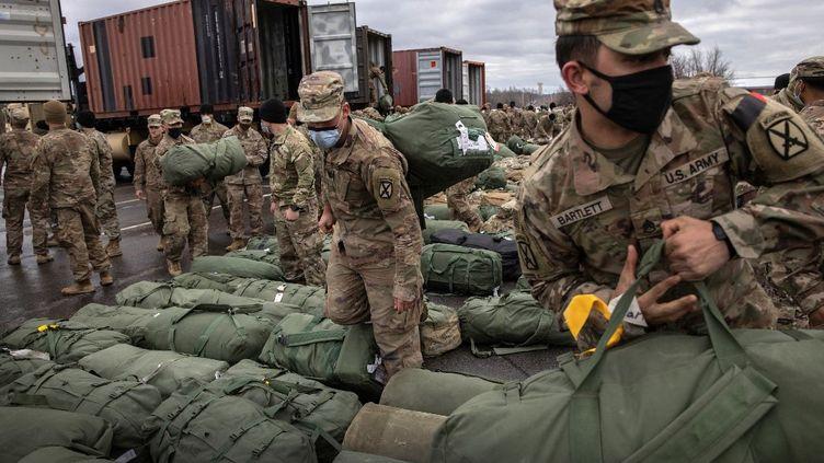 Des soldats récupèrent leurs bagages à leur arrivée à Fort Drum (New York, Etats-Unis), le 10 décembre 2020, après un déploiement de neuf mois en Afghanistan. (JOHN MOORE / GETTY IMAGES NORTH AMERICA / AFP)