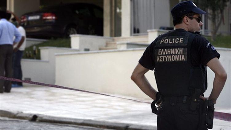 Un policier devant le domicile du journaliste Socratis Guiolas, assassiné lundi 19 juillet 2010 à Athènes. (AFP - Angelos Tzortzinis)
