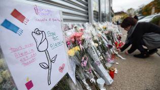 Une femme vient déposer des fleurs en mémoire d'Alexia Daval, la joggeuse tuée en Haute-Saône, le 2 novembre 2017. (SEBASTIEN BOZON / AFP)