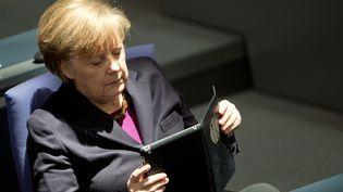 La chancelière allemande Angela Merkel lit sa tablette numérique, le 20 mars 2014, au Bundestag de Berlin (Allemagne). (BERND VON JUTRCZENKA / DPA)