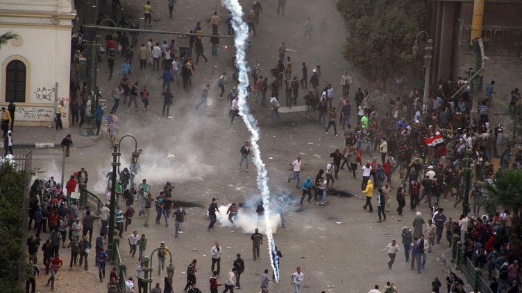 Les policiers tirent des grenades lacrymogènes pour disperser les manifestants, le 23 novembre 2012, au Caire (Egypte). (AHMED MAHMOUD / AFP)