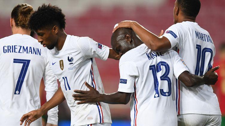 L'équipe de France félicite Ngolo Kanté (n°13), auteur du but vainqueur contre le Portugal, samedi 14 novembre. (PATRICIA DE MELO MOREIRA / AFP)