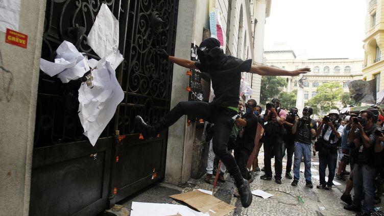 Un manifestant donne des coups de pied dans la porte d'entrée du conseil municipal à Rio (Brésil), le 1er octobre 2013, lors d'une manifestation d'enseignants en grève. (PILAR OLIVARES / REUTERS)