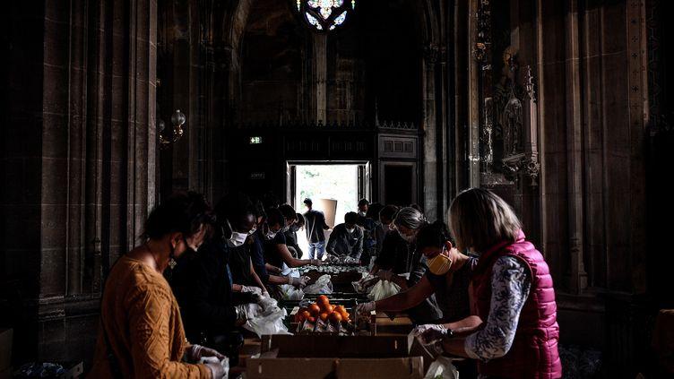 Des volontaires de l'association Solidarités Saint-Bernard préparent une distribution alimentaire à l'intérieur de l'église Saint-Bernard, à Paris, le 6 mai 2020. (CHRISTOPHE ARCHAMBAULT / AFP)