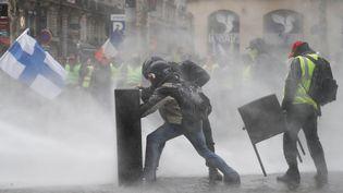 Les manifestants se protègent des jets d'eau, au centre de l'avenue des Champs-Elysées. (FRANCOIS GUILLOT / AFP)