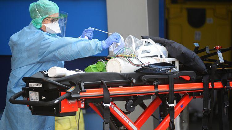 Une anesthésiste désinfecte du matériel médical qui a servi à amener six malades du coronavirus à l'hôpital de Brest, le 24 mars 2020. (JEAN-FRANCOIS MONIER / AFP)