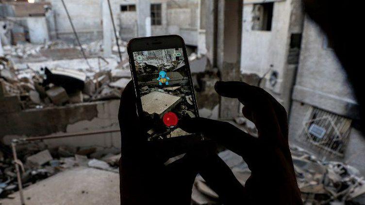 Un utilisateur de Pokémon Go dans les décombres de la ville de Douma, près de Damas en Syrie. (Sameer Al-Doumy / AFP)