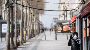 Même image surprenante sur les Champs-Elysées, à Paris, immortalisés vides par cette touriste le 17 mars 2020. (MARTIN BUREAU / AFP)