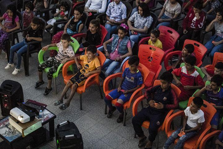 Les enfants profitent d'une séance de cinéma grâce au cinéma itinérant du réalisateur Shero Hinde. (DELIL SOULEIMAN / AFP)