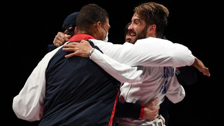 Romain Cannone exulte avec ses entraîneurs après son titre olympique, le 25 juillet 2021. (MOHD RASFAN / AFP)