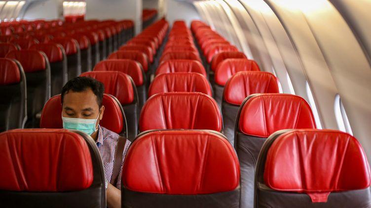Un passager bien solitaire dans un avion (photo d'illustration, 1er février 2020). (ADAM TANJUNG / AFP)