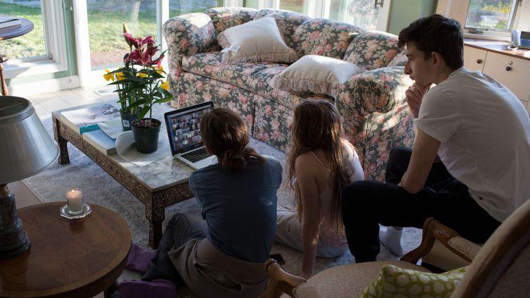 Une famille réunie autour d'un appel en visio, le 11 avril 2020 dans le Connecticut (Etats-Unis). (ANDREW LICHTENSTEIN / CORBIS NEWS)