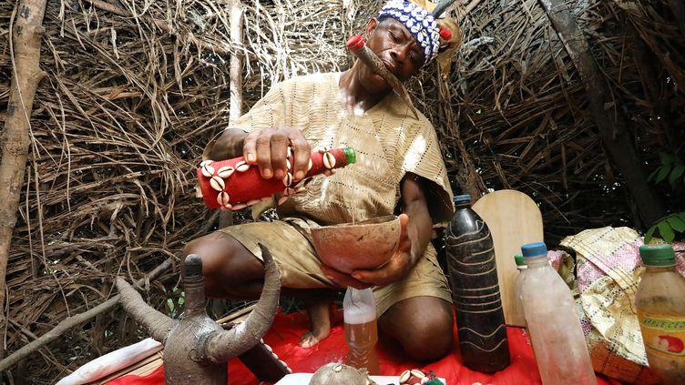 Ce guérisseur du village de Magbumoh en Sierra Leone mélange des herbes dans une potion. Il tient dans sa bouche la corne d'un animal pour communiquer avec les dieux qui le guident. Les jeunes Sierra-Léonais doivent parfois subir à la fin de l'année scolaire des rites d'initiation secrets susceptibles de provoquer descicatrices et des troubles qui peuvent durertoute la vie. (LYNN ROSSI / AFP)