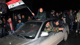 Des Syriens célèbrent la reprise totale d'Alep, annoncée par le régime de Bachar al-Assad, le 22 décembre 2016 (GEORGE OURFALIAN / AFP)