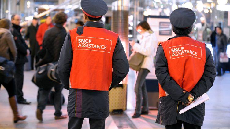 Des employés de la SNCF se tiennent à la disposition des usagers sur un quai de la gare du Nord à Paris, le 12 décembre 2011, dans le cadre du changement des horaires de trains sur l'ensemble du réseau. (ERIC PIERMONT / AFP)