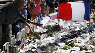Une femme dépose un bouquet de fleurs sur la promenade des Anglais, dimanche 17 juillet 2016 à Nice (Alpes-Maritimes). (PASCAL ROSSIGNOL / REUTERS)