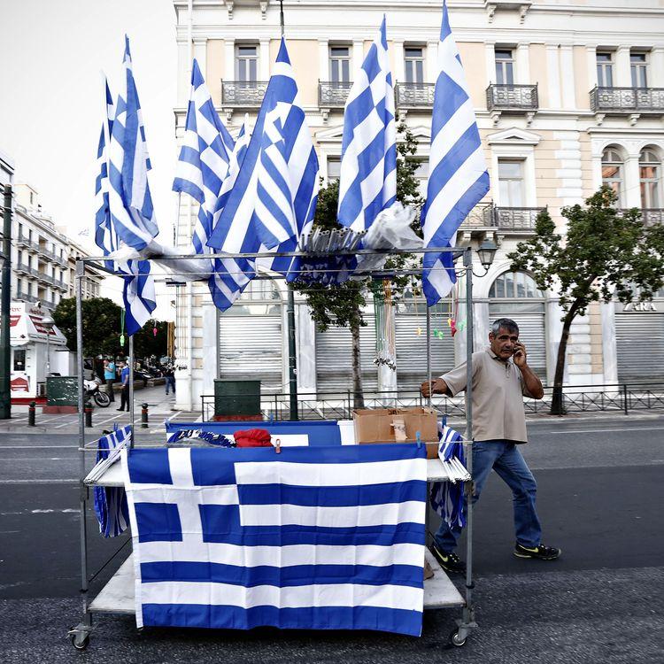 Un vendeur de drapeaux de la Grèce, le 5 juillet 2015 dans les rues d'Athènes (Grèce). (ALEXANDROS MICHAILIDIS / SOOC / AFP)