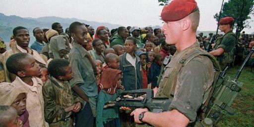 Deux soldats français montent la garde devant des réfugiés tutsis, le 30 avril 1994, dans le camp de Niashishi. (PASCAL GUYOT / AFP)