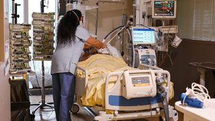 Une soignante prodigue des soins à un patient atteint du coronavirus Covid-19 et placé en soins intensifs. (BERTRAND GUAY / AFP)