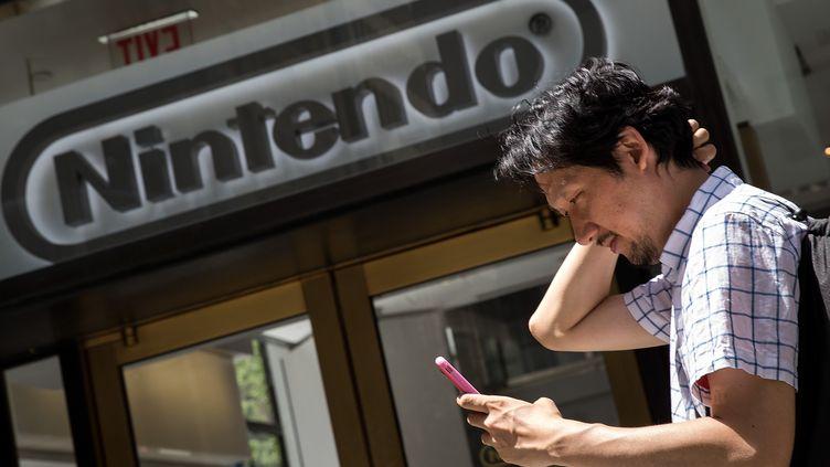 """Un homme joue à """"Pokémon Go"""" devant un magasin Nintendo, à New York (Etats-Unis), le 11 juillet 2016. (DREW ANGERER / AFP)"""