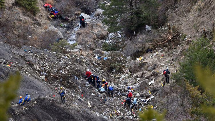 Des enquêteurs fouillent le site du crash de l'avion de Germanwings, dans les montagnes proches de Seyne (Alpes-de-Haute-Provence), le 26 mars 2015. (ANNE-CHRISTINE POUJOULAT / AFP)